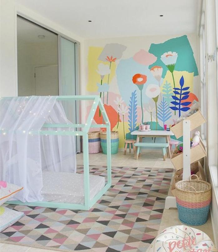 tapis à triangles multicolores, lit bébé montessori vert maisonnette, ciel de lit, mur d accent motifs fleurs, panier à jouets, table basse , banc en bois, tabouret, mur couleur blanche