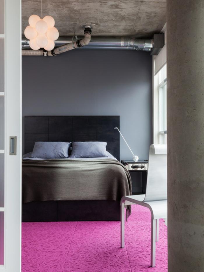 chambre rose et gris, mur couleur gris anthracite, lit gris foncé, linge de lit bleu et gris, tapis rose magenta, plafond en béton et tyuaux style industriel