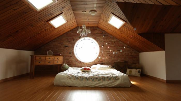 toiture et revêtement sol en bois, poutres, matelas blanc, couverture de lit multicolore, lucarne, bureau en bois vintage, lustre élégant, amenagement comble