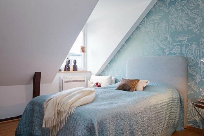 mur d accent, papier peint bleu à motifs floraux, lit gris, couverture de lit bleue, parquet clair, couleur mur blanc, déco chambre sous pente