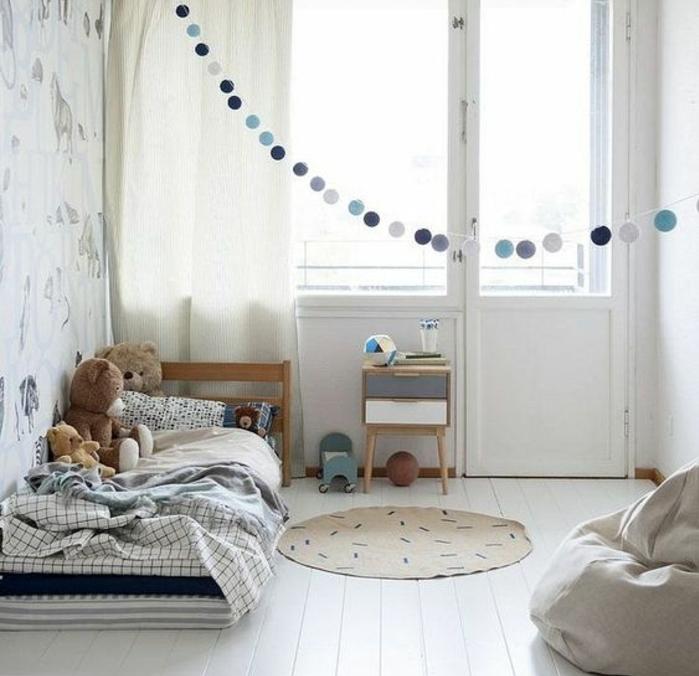 parquet blanchi, matelas à même le sol, peluche ourson, table de nuit avec tiroirs, papier peint motifs lion, rideau blanc cassé, pédagogie montessori