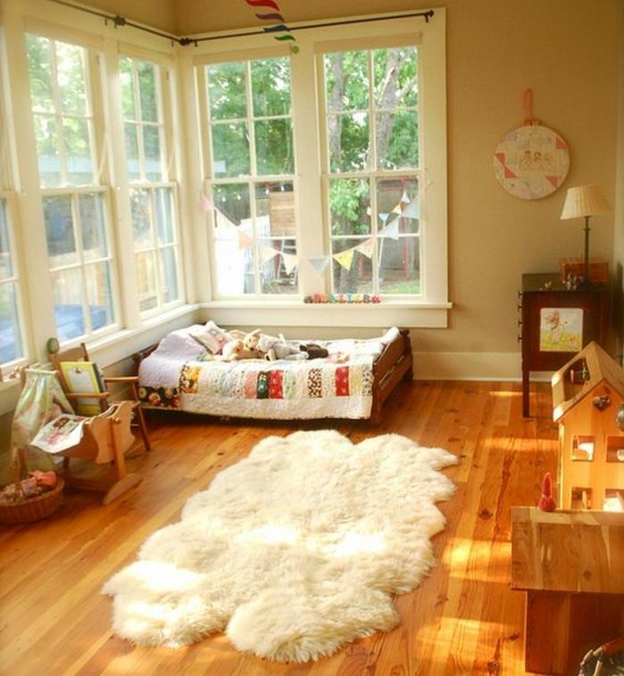 parquet en bois, tapis blanc, lit bébé montessori au sol, petite chaise, maisonnettes en bois, mur couleur beige, méthode montessori