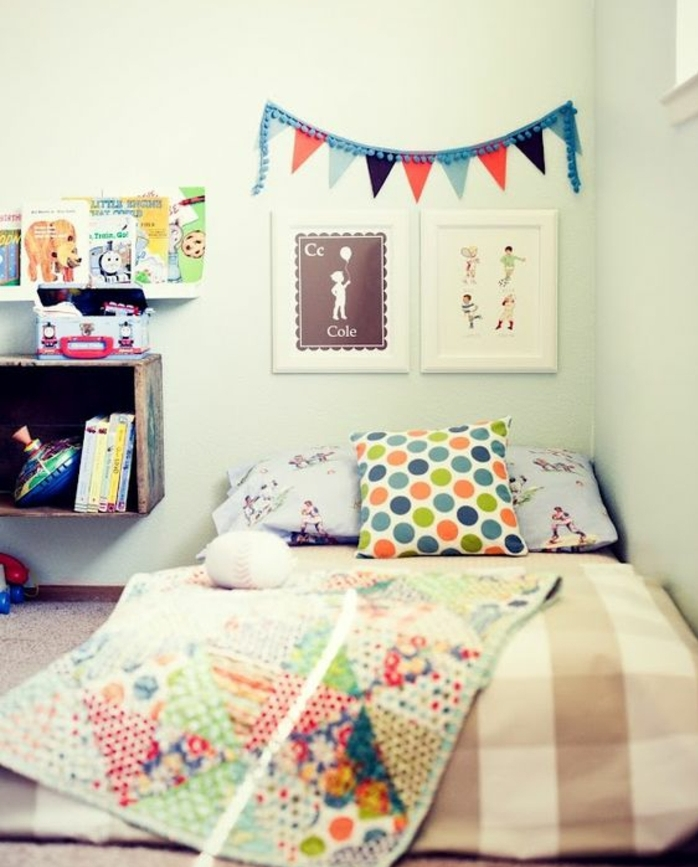 mur couleur blanche, coussins et couverture de lit multicolores, deco murale, dessins, etagere rangement livres, meuble bas, exemple chambre montessori