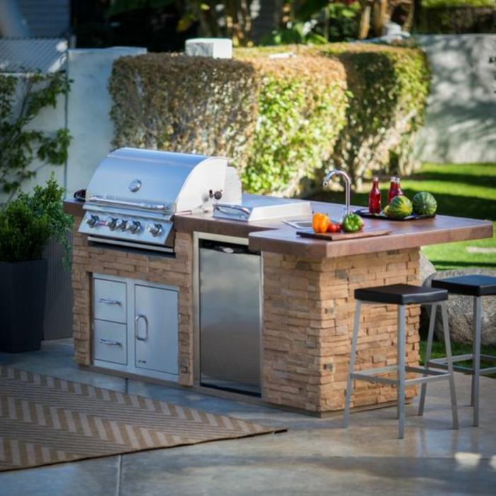 une cuisine d'extérieure compact et fonctionnel en pierre naturelle équipée d'un barbecue