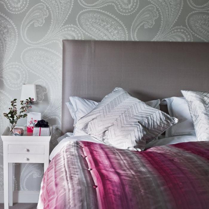 papier peint gris à motifs blancs, table de nuti blanche avec tiroit, parure de lit gris, rose et blanc, coussins blancs, lit gris, idée déco chambre adulte