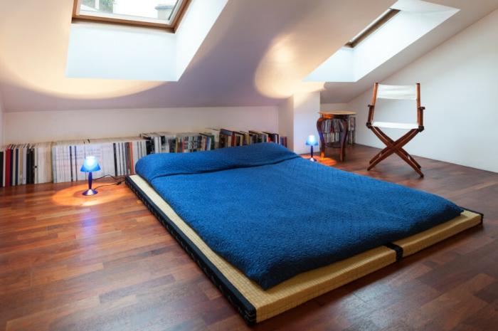 lit à même le sol, parquet en bois marron, linge de lit bleu, rangement livres sur le sol, chaise pliable, peinture mur blanc, déco chambre sous pente