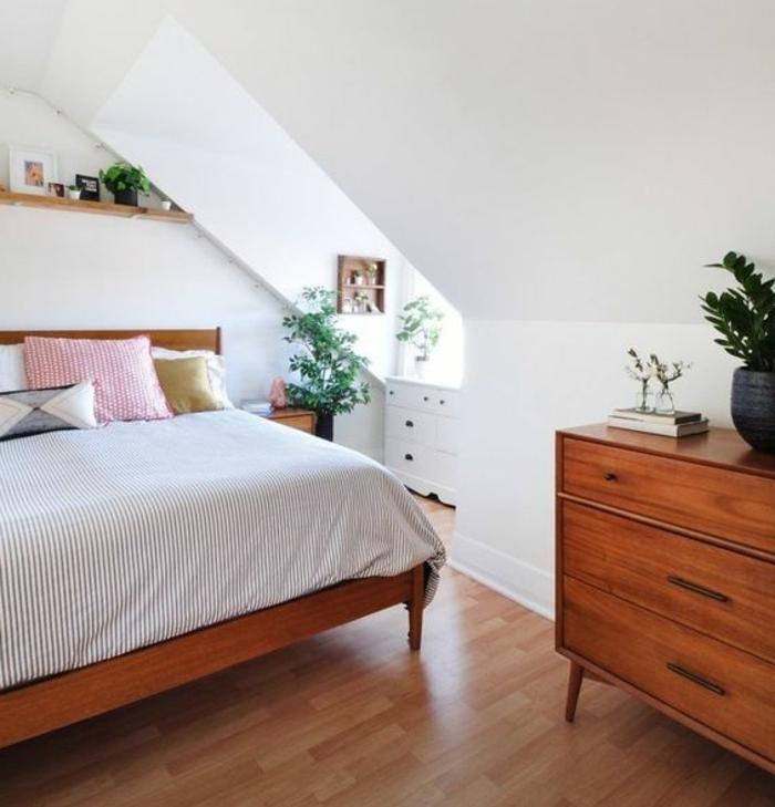 parquet stratifié en bois, commode en bois, lit en bois, linge de lit à rayures, coussins de taille et couleur différente, plantes, étagère, chambre mansardée