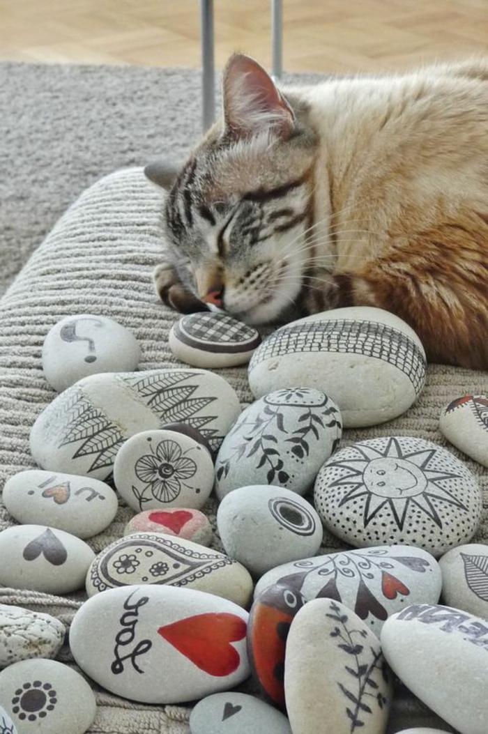 peindre des galets, chat qui dort et plusieurs galets décorés