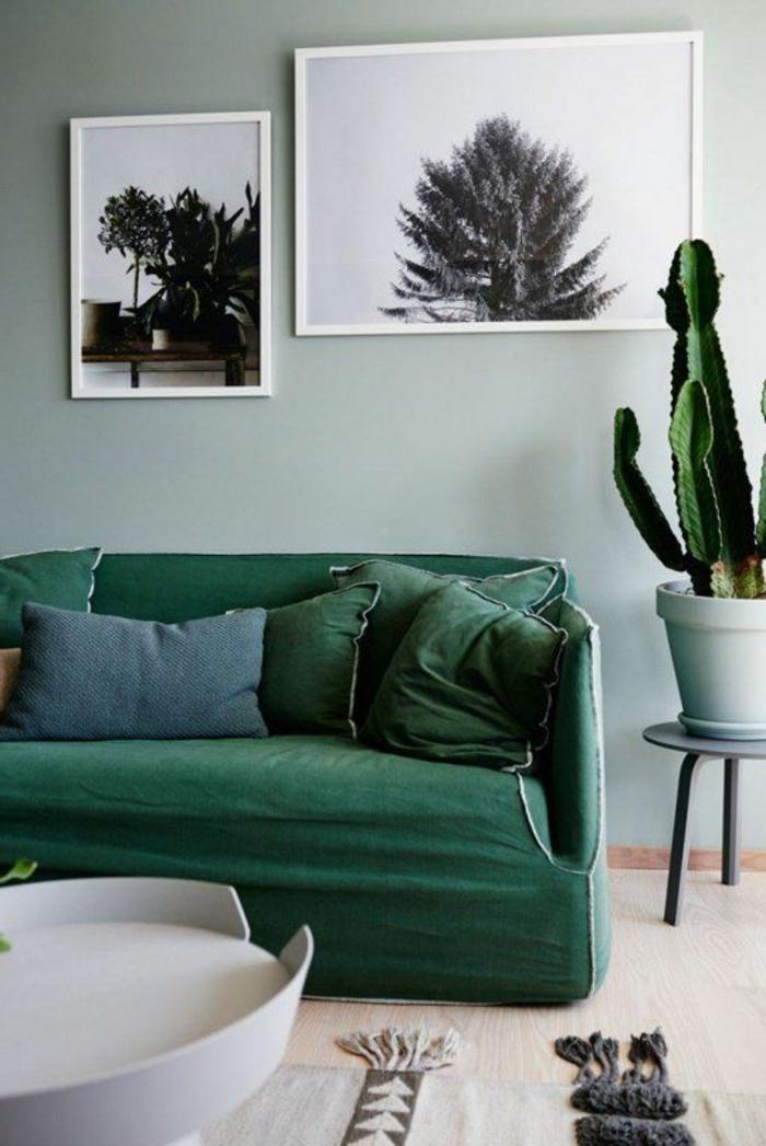 peinture glycéro, sofa vert avec plusieurs coussins, cactus et tableaux avec peintures monochromes