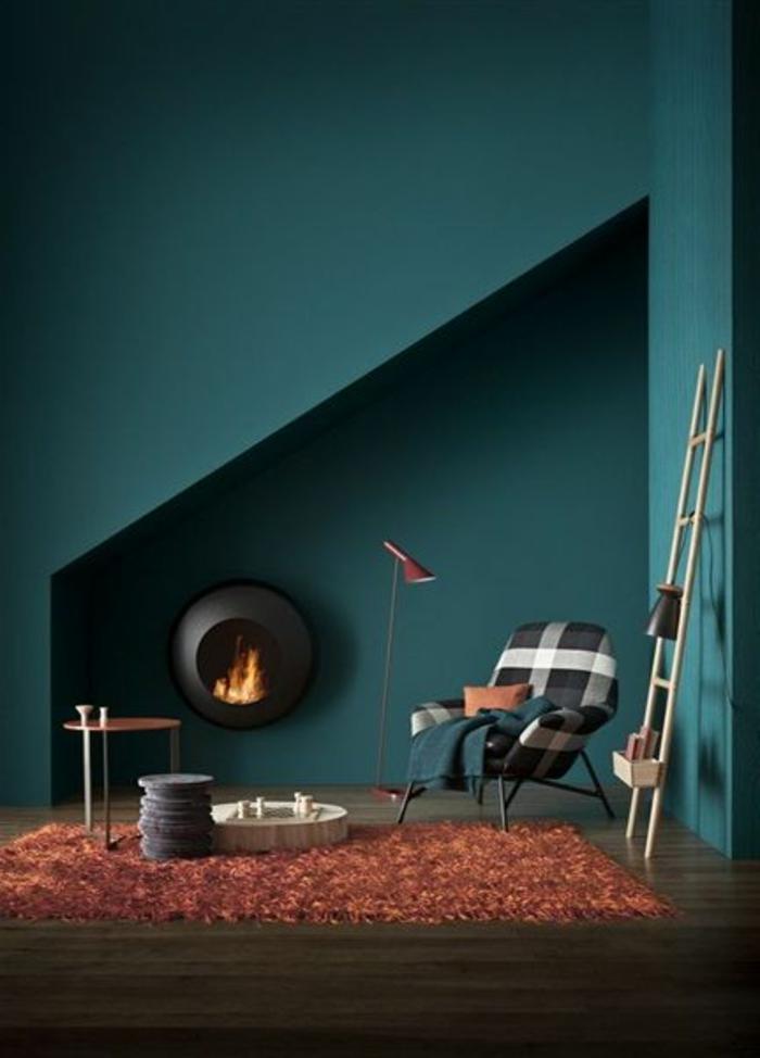 peinture bleu canard, tapis rouge, cheminée ronde décorative, échelle en bois