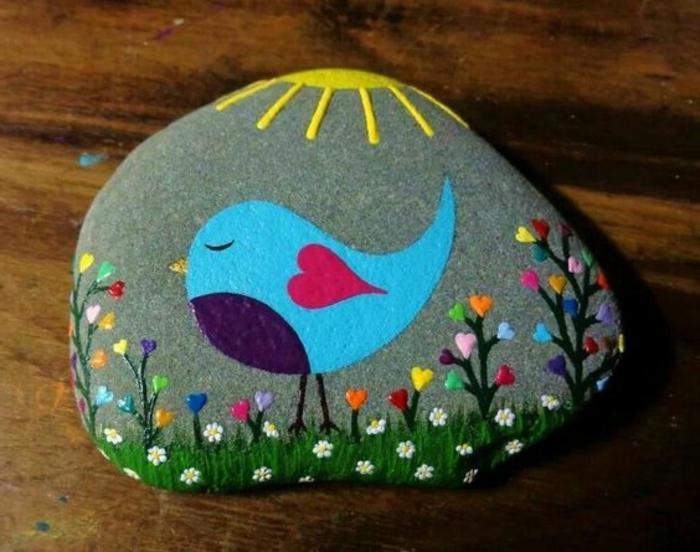 peinture sur galet, pelouse verte, fleurs et un oiseau