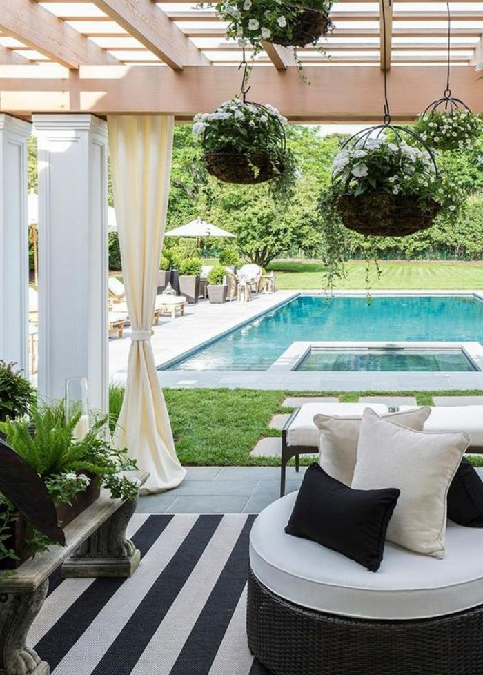 un pergolas en bois décoré en noir et blanc, contour piscine en dalles grises