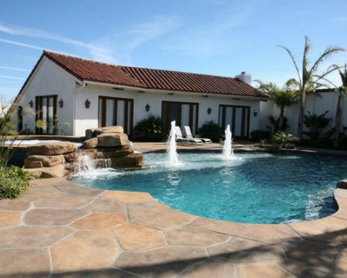 jolie piscine avec faux rochers et cascade, contour piscine en béton décoratif effet pierre