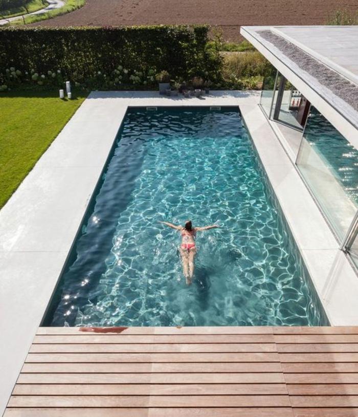 une plage de piscine bois composite, un couloir de nage aux abords en béton