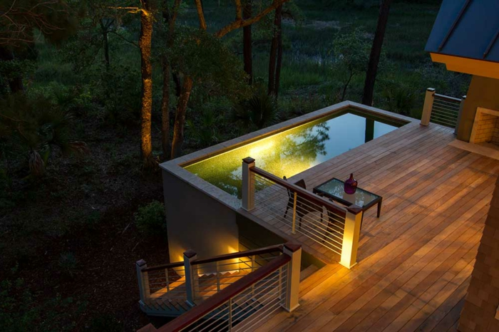 piscine hors sol rectangulaire, terrasse de piscine en bois, éclairage de piscine jaune, table basse, vue sur la forêt