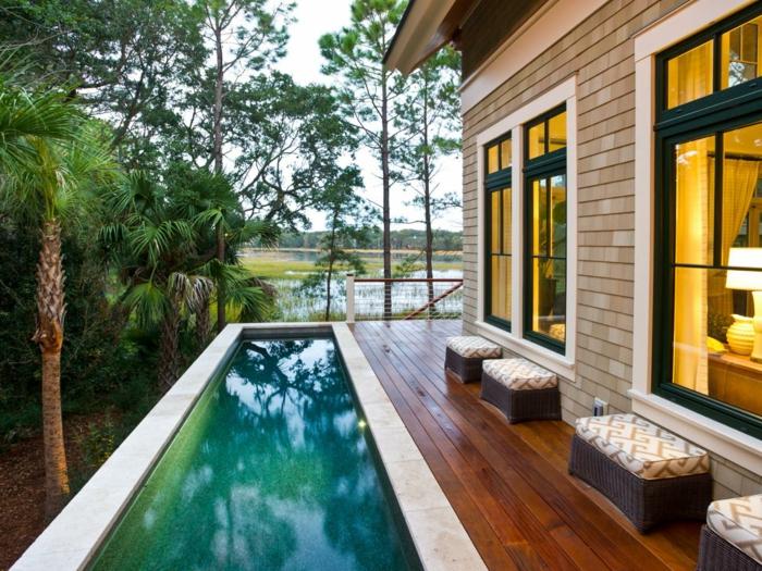piscine surélevée, tabourets marron, grandes fenêtres, palmier tropical, clôture en bois