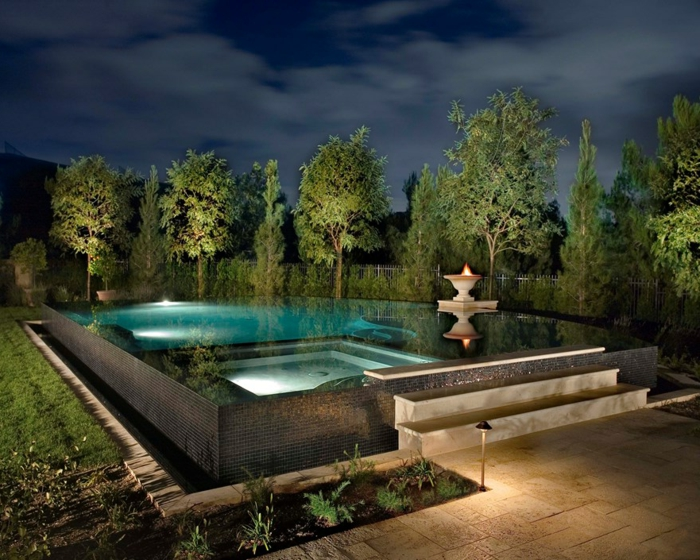 piscine hors sol rectangulaire, éclairage de nuit, fontaine avec feu, arbres verts