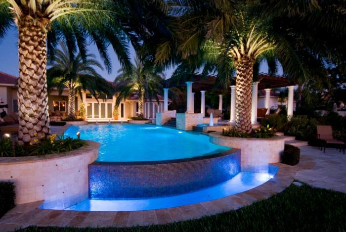 piscine hors sol rectangulaire, éclairage bleu, palmier tropical, colonnes blanches, piscine en mosaique