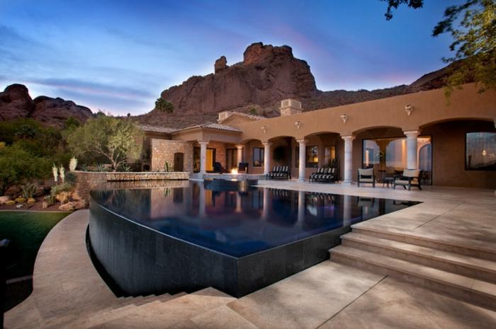 piscine surélevée, façade de maison en beige, murs en pierre, salon de jardin en blanc et noir