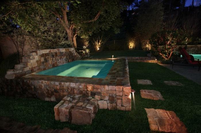 piscine surélevée en pierre, gazon ray grass, éclairage de piscine, arbres, transats