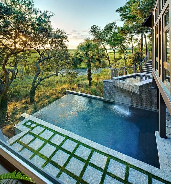 piscine surélevée, arbres, rampe en verre, cascade d'eau, maison en bois, gazon vert