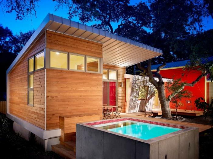 piscine surélevée en béton, maison en bois, mur rouge, table de jardin en bois