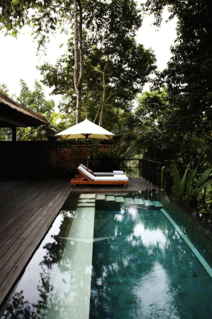 une piscine immergée équipée d'un entourage piscine en bois foncé