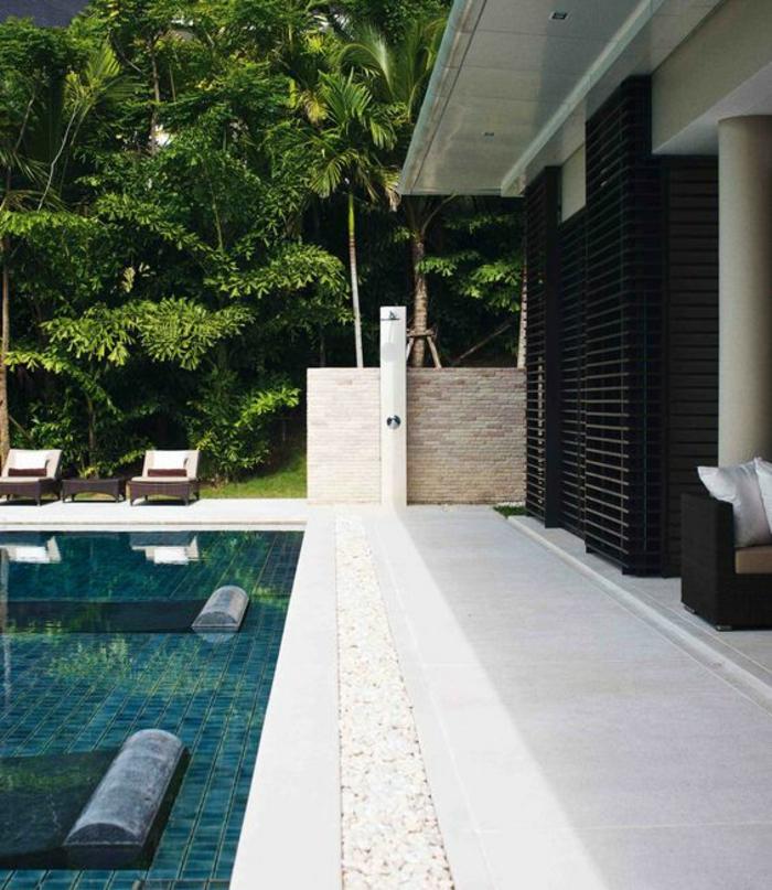 piscine au design contemporain et au revêtement de sol en carreaux vertes, entourage piscine en pierre reconstituée