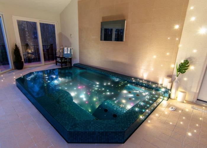 piscine hors sol rectangulaire, façade de maison beige, grandes fenêtres, lanternes à bougies