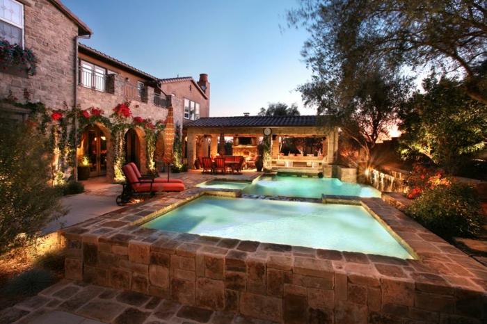 piscine hors sol rectangulaire, maison rurale en pierre, matelas de transat rouges, végétation grimpante