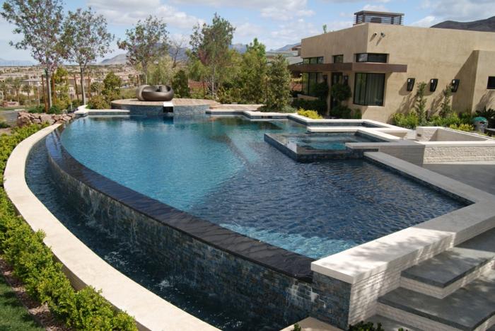 piscine hors sol, cascades d'eau, façade de maison beige, piscine surélevée