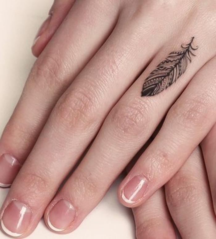 jolie plume tatouée sur le doigt, un tatouage main femme subtile