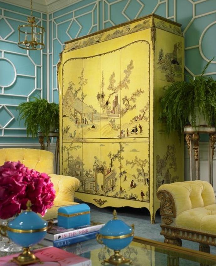 relooker armoire ancienne, armoire repeinte en jaune, motifs chinoiseries, canapé, fauteuil jaune, table en verre, mur couleur bleue, bouquet de fleurs, salon oriental, exotique