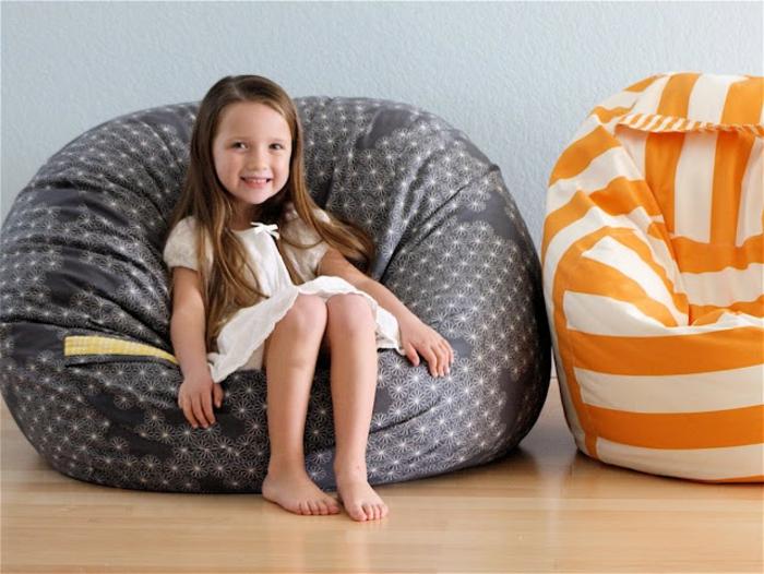 fabriquer un pouf, parquet en bois, petite fille, robe blanche, pouf orange et blanc