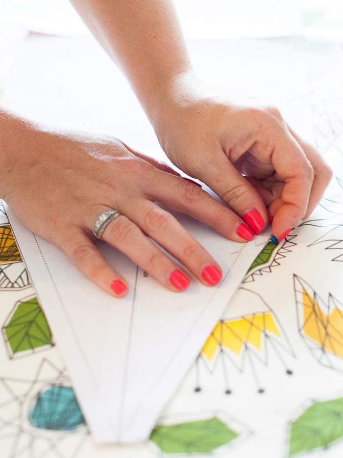 fabriquer un pouf, manucure rouge, tissu blanc à décoration multicolore, bague argent, tuto pouf