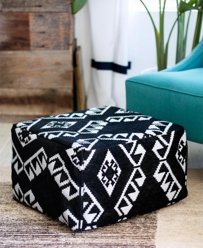 pouffe geant, tapis beige et marron, armoire en bois, fauteuil turquoise, plante verte