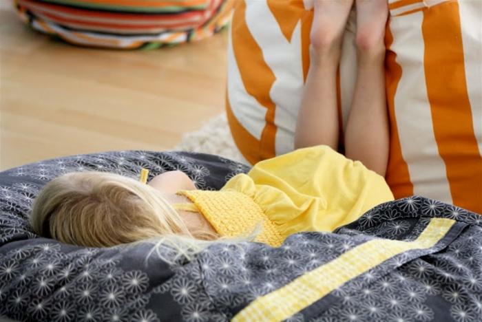 pouf pour enfant, fille blonde, robe jaune pastel, pouf bleu à motifs floraux, pouf orange