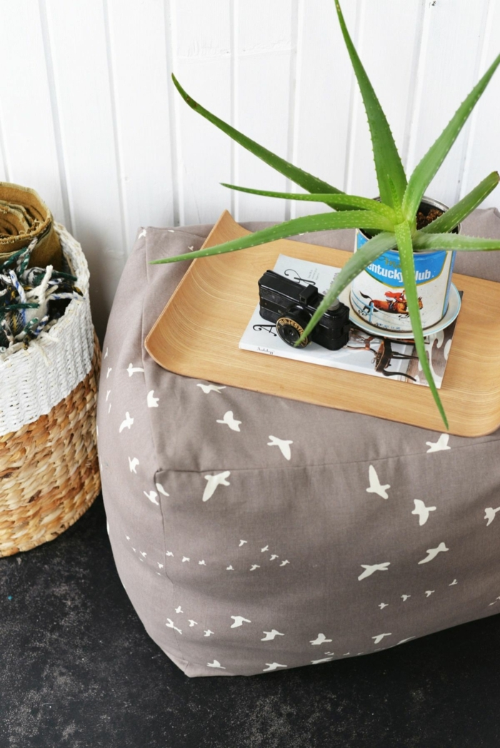 pouffe geant, tapis moelleux, fleur verte, murs blancs en palettes