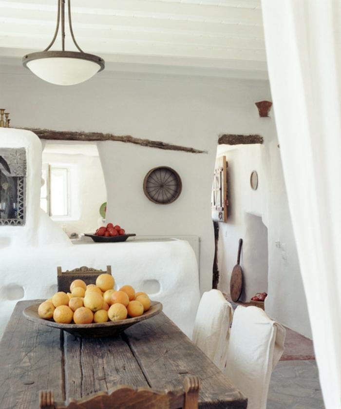 décoration grecque, murs blanc, décoration en pierre et bois, citrons, table ancienne en bois
