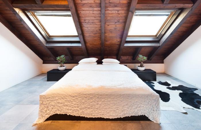 carrelage effet bois, couverture de lit blanche, tapis vache, peinture mur blanchem plafond en bois marron, fenêtres de combles, amenagerment combles