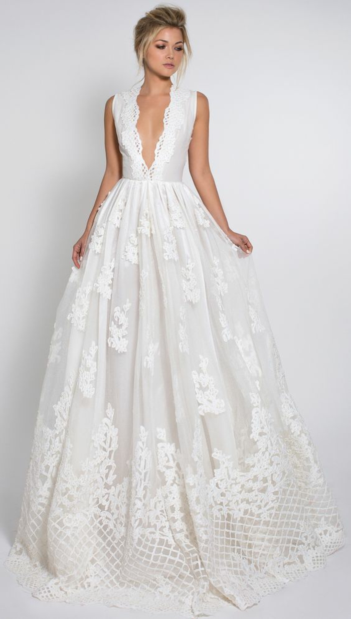 une robe de mariée simple et chic à jupe bouffante, détails en dentelle, encolure à v