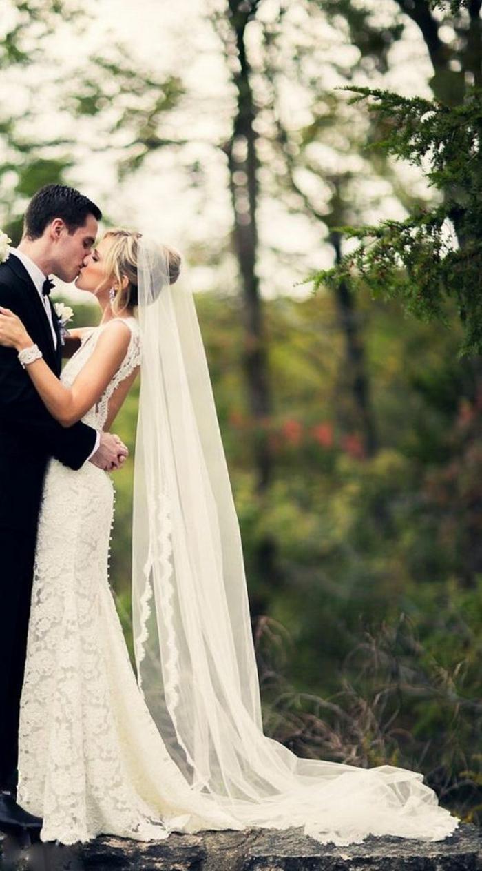 une jolie robe de mariée en dentelle associée avec long voile mariée à bordure en dentelle