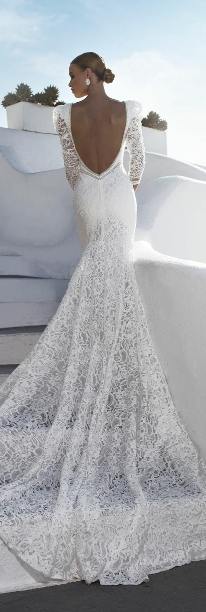 robe de mariée moulante avec bas évasé et dos décolleté, un chignon bas élégant