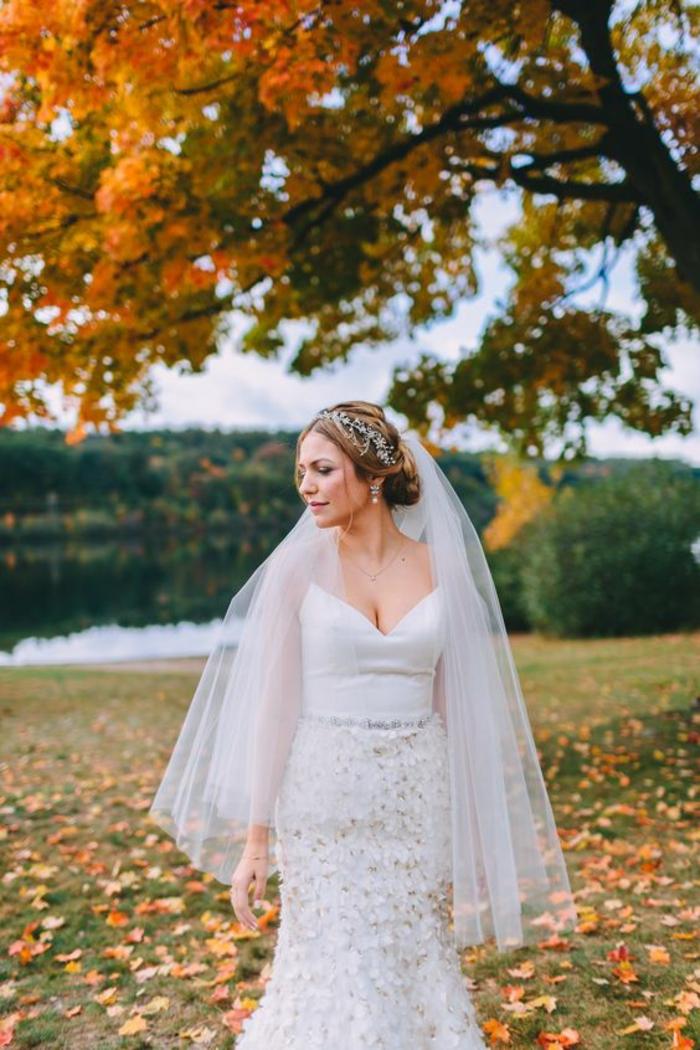 une coiffure de mariée élégante à bijou combinée avec un voile du bout des doigts