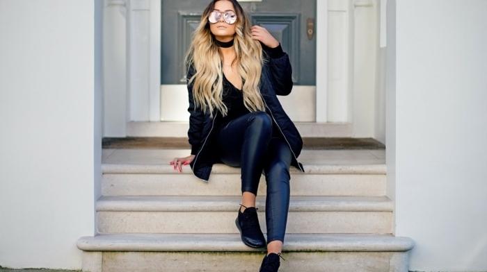 chemise noire, cheveux blonds bouclés, pantalon noir en cuir, col ras du cou