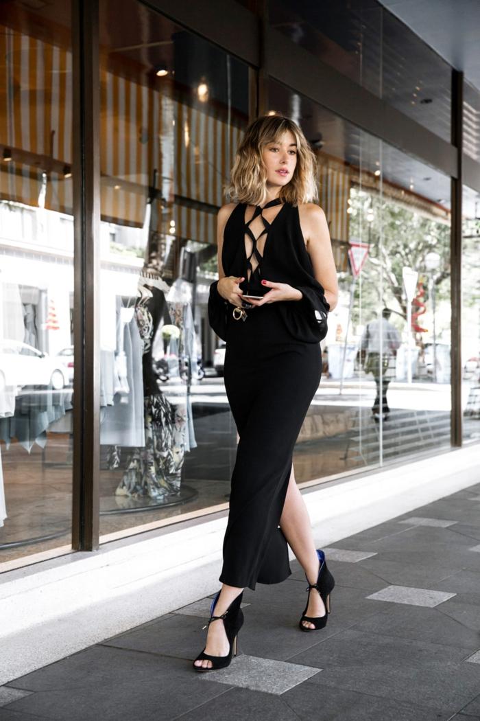vetement noir, robe avec décolleté à lacets, cheveux blonds, sandales noires, manucure rouge