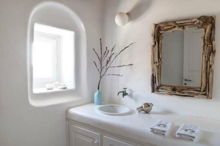 salle de bain grecque, petite fenêtre blanche, cadre miroir en branchettes, fleurs séchées, lavabo en marbre