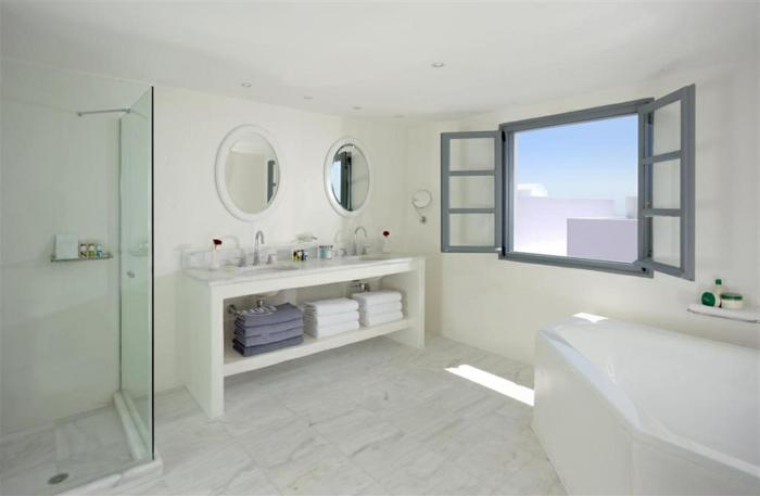 décoration grecque, carrelage marbre, miroir rond, volets gris, baignoire blanc, cabine de douche
