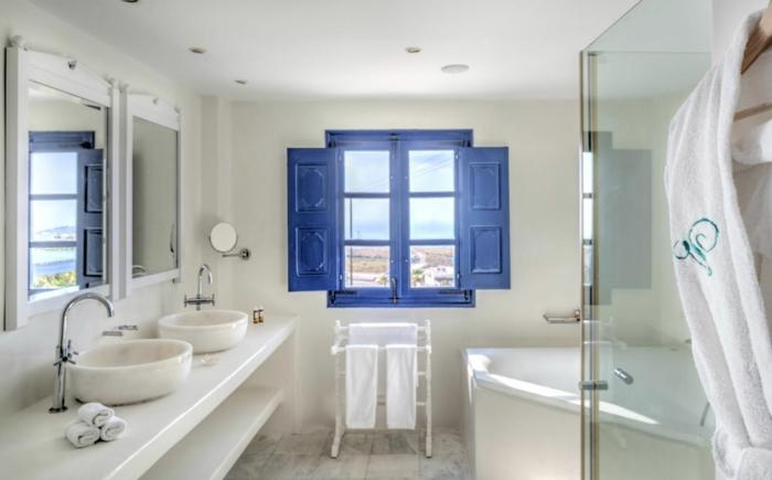 bleu grec sur les volets, lavabo en marbre, baignoire blanc, grand miroir