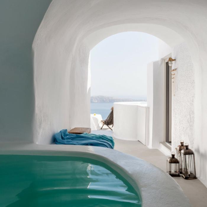 décoration grecque, vue sur la mer, murs blancs, arc, serviette bleu, banc en bois